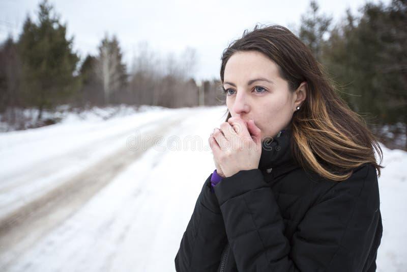 Het meisje verwarmt haar handen door adem in wintertijd royalty-vrije stock afbeelding