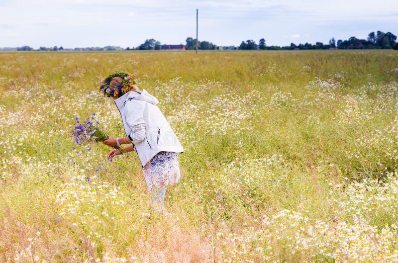 Het meisje verzamelt bloemboeketten op het gebied royalty-vrije stock afbeelding