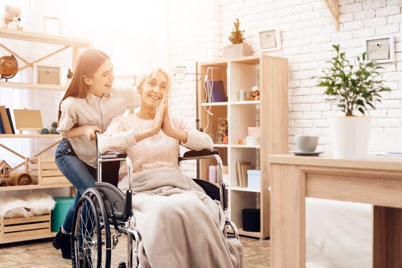 Het meisje verzorgt thuis bejaarde Het meisje berijdt vrouw in rolstoel De vrouw geniet zich van royalty-vrije stock fotografie