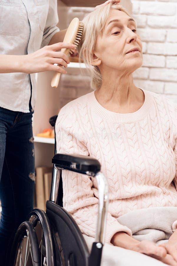Het meisje verzorgt thuis bejaarde Het meisje borstelt vrouwen` s haar stock afbeeldingen