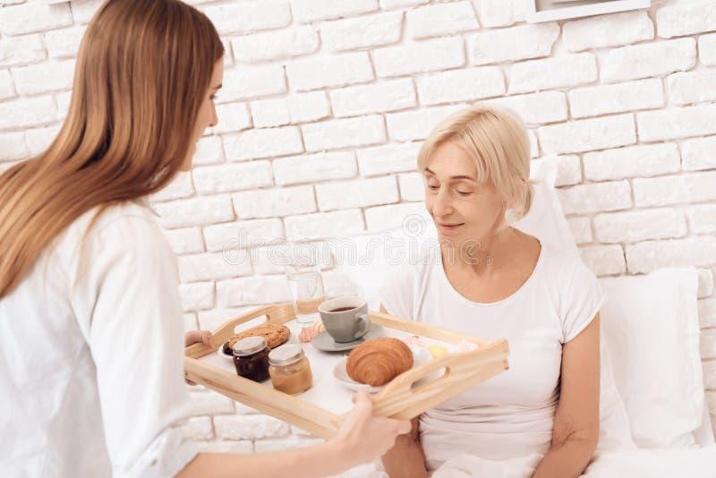 Het meisje verzorgt thuis bejaarde Het meisje brengt ontbijt op dienblad royalty-vrije stock foto's