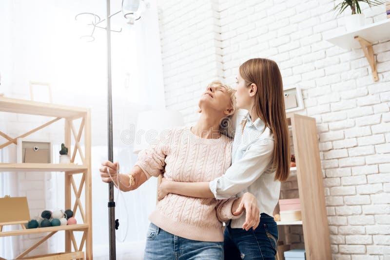 Het meisje verzorgt thuis bejaarde De vrouw bevindt zich met hulp van dalings tegenpool royalty-vrije stock foto