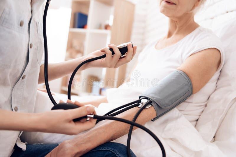 Het meisje verzorgt thuis bejaarde Het meisje gebruikt tonometer om bloeddruk te meten stock afbeeldingen