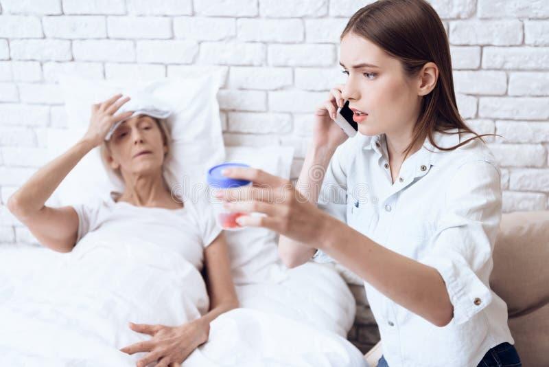 Het meisje verzorgt thuis bejaarde Het meisje is op telefoon, die pillen geven aan vrouw royalty-vrije stock foto