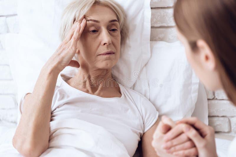 Het meisje verzorgt thuis bejaarde Zij houden handen De vrouw voelt slecht stock fotografie
