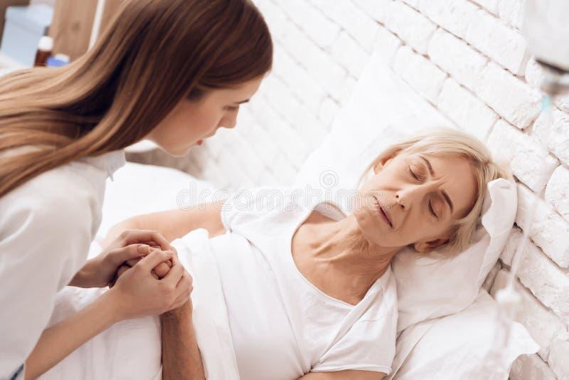 Het meisje verzorgt thuis bejaarde Zij houden handen De vrouw voelt slechter stock foto's