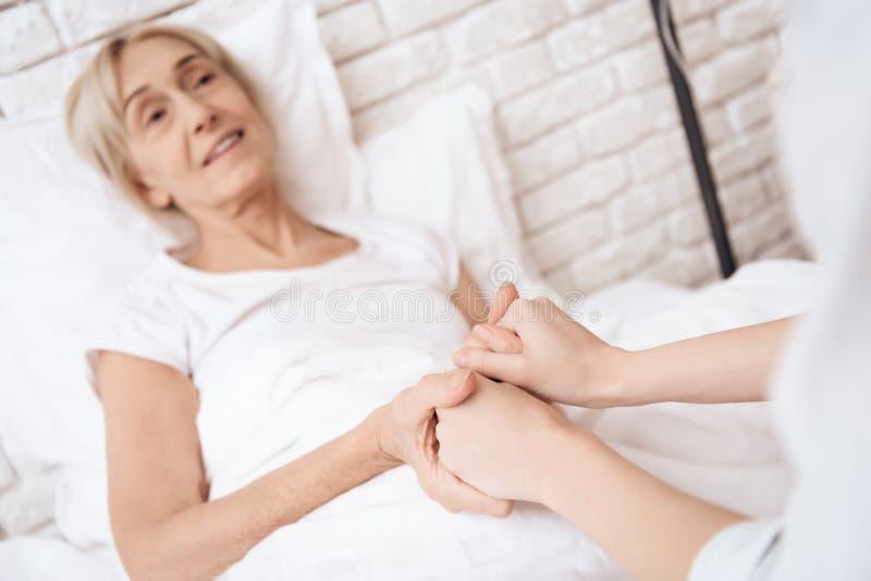 Het meisje verzorgt thuis bejaarde Zij houden handen De vrouw voelt zich beter royalty-vrije stock foto