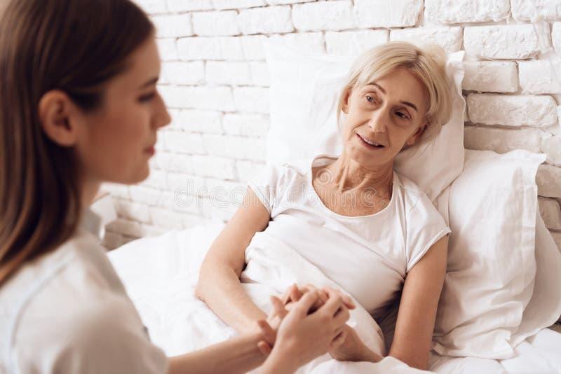Het meisje verzorgt thuis bejaarde Zij houden handen De vrouw voelt zich beter stock foto