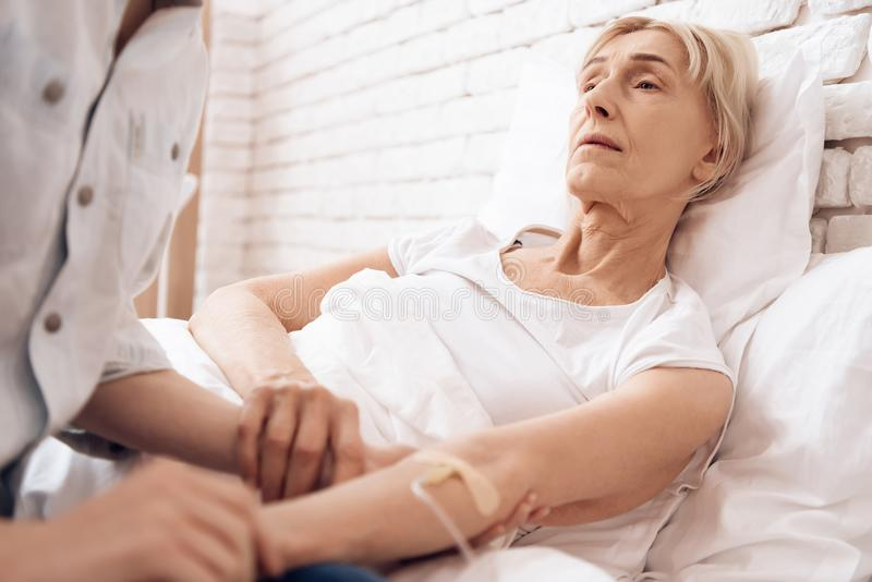 Het meisje verzorgt thuis bejaarde Zij houden handen De vrouw wordt verbonden met dalingsteller stock foto's