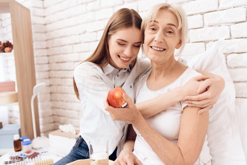 Het meisje verzorgt thuis bejaarde Zij omhelzen De vrouw houdt appel stock fotografie