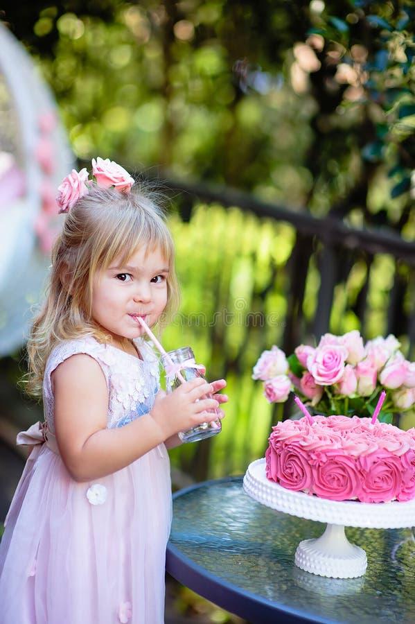 Het meisje viert Gelukkige Verjaardagspartij met roze openlucht stock foto
