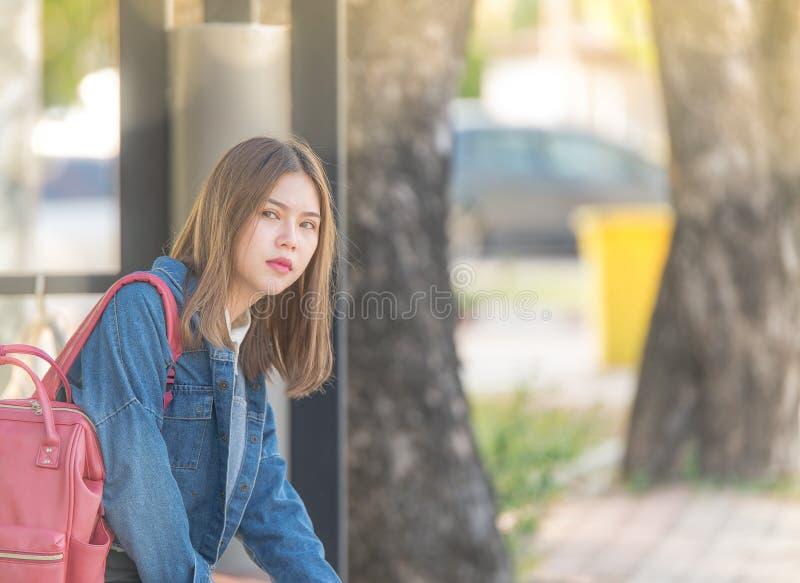 Het meisje wacht op een bus Bored tiener die op ouders openlucht op de zitting van de metaalbank wachten stock fotografie