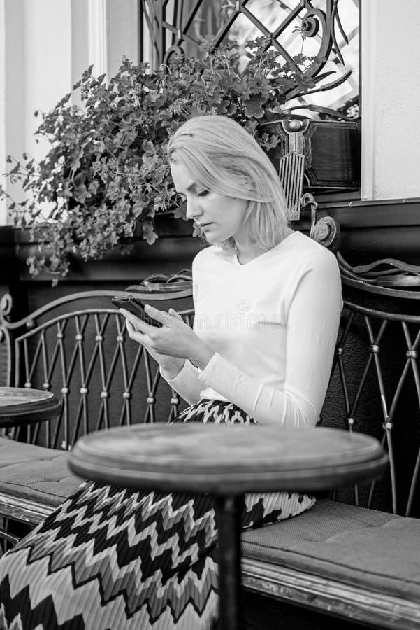 Het meisje wacht vergadering met vrienden Schik benoeming in sociaal netwerk Doe benoeming Vrouwen bezig gezicht met smartphone stock fotografie