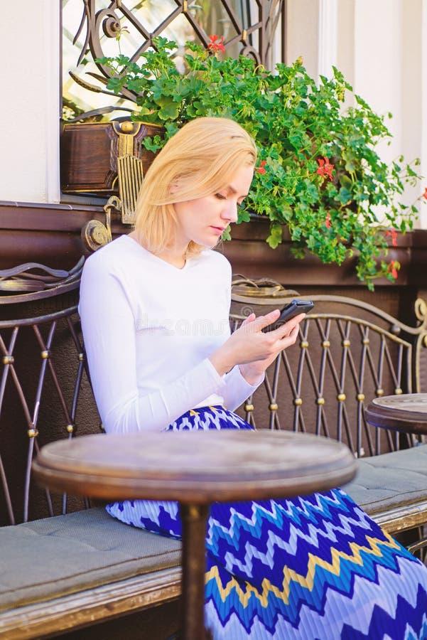 Het meisje wacht vergadering met vrienden Schik benoeming in sociaal netwerk Doe benoeming Vrouwen bezig gezicht met smartphone stock afbeeldingen