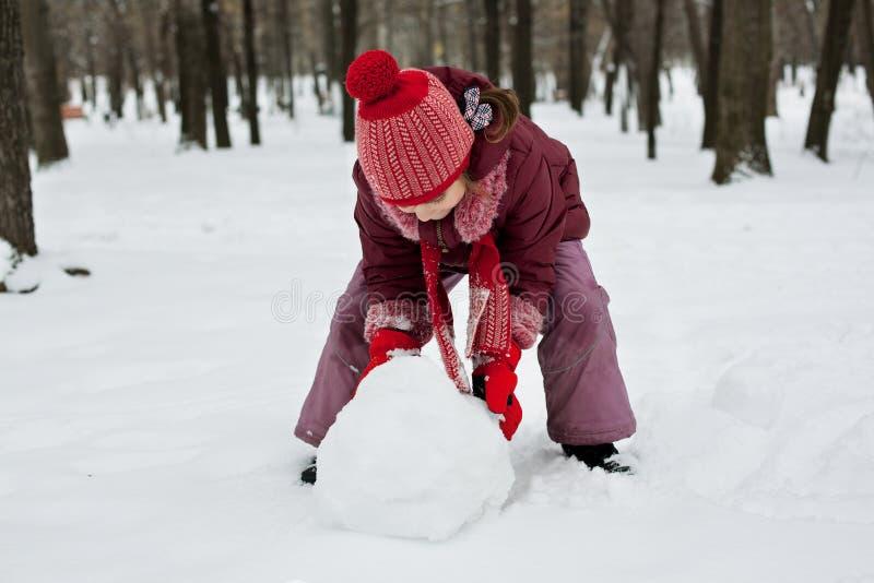 Het meisje was liggend een sneeuwman stock afbeeldingen