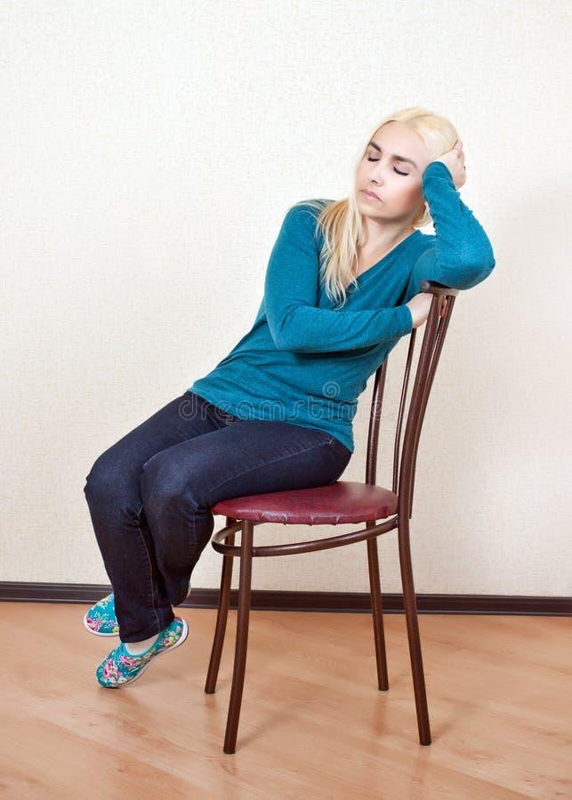 Het meisje was in slaap zitting op een stoel stock foto