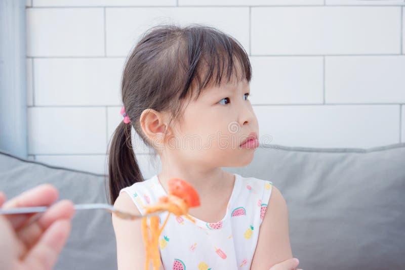 Het meisje weigert om tomaat in spagethi van haar moeder te eten stock foto's