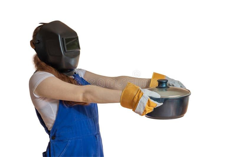 Het meisje in werkkledij en een lassenmasker houdt een pan in Ha stock afbeeldingen