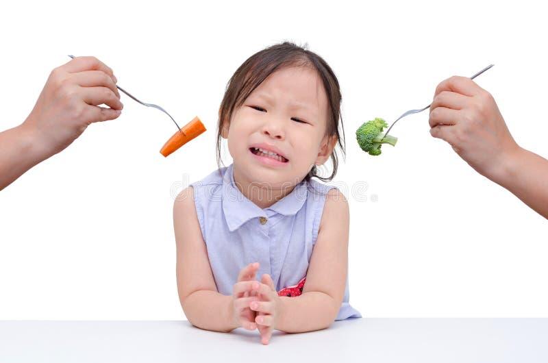 Het meisje wil geen groenten eten stock fotografie