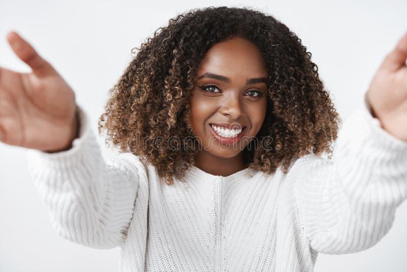 Het meisje wil omhelzingen verwarmen Teder en leuk Afrikaans-Amerikaans wijfje die in sweater handen naar camera uitbreiden tot k stock fotografie