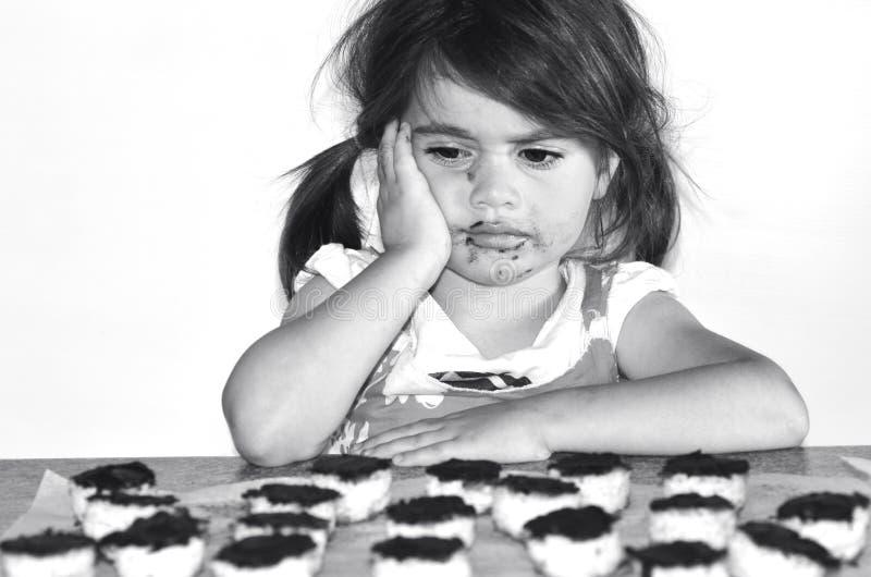 Het meisje wil veel chocoladekoekjes eten stock afbeeldingen