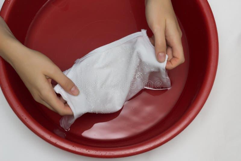 Het meisje wist kinderen ` s de witte T-shirt in een rood bassin van vlekken, van vlekkenmiddel, close-up, handen witte achtergro stock fotografie