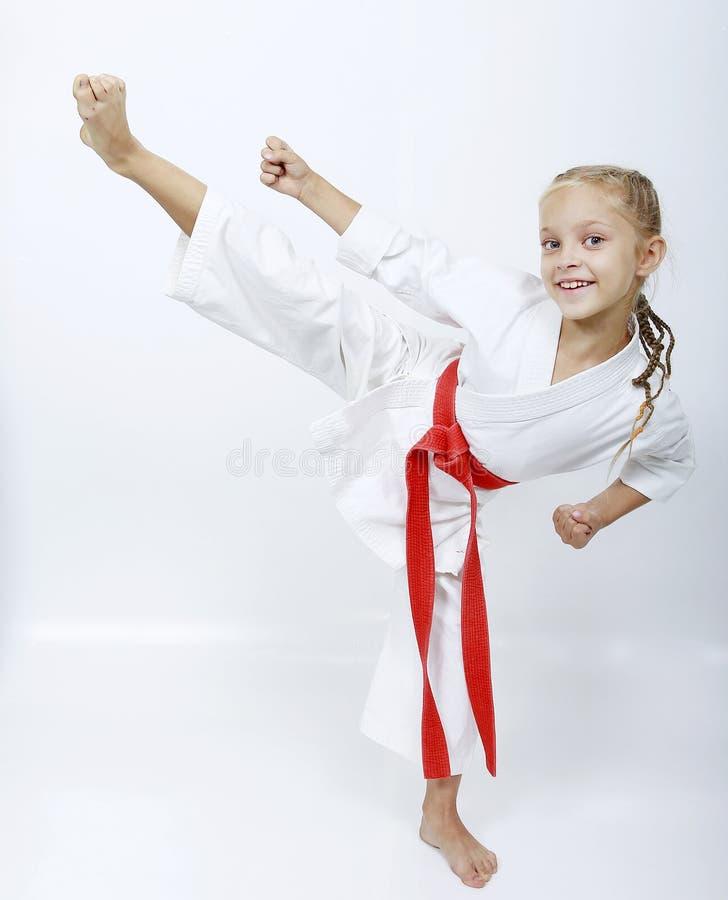 Het meisje in witte kimono met een rode riem slaat het schoppen royalty-vrije stock foto