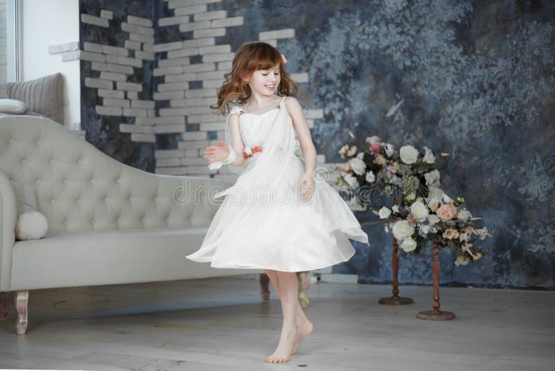 Het meisje in witte kleding dansing en beweegt zich stock afbeelding