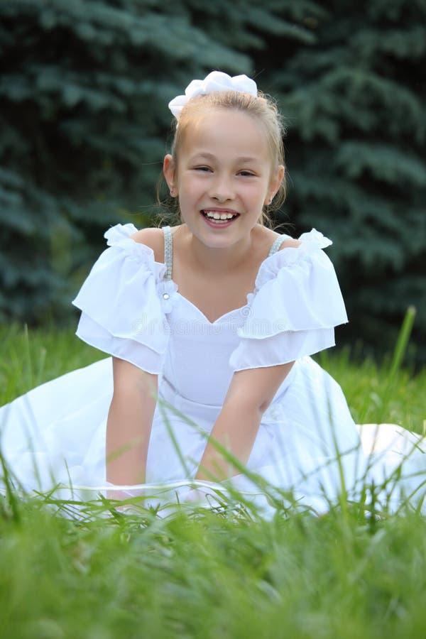 Het meisje in witte kleding zit op gazon stock foto