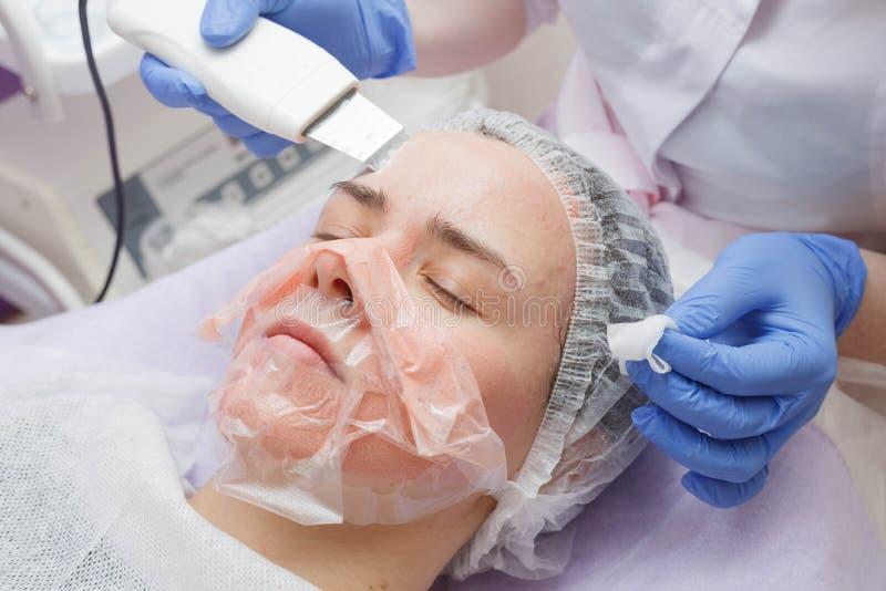 Het meisje wordt aangeboden de schoonmakende dienst van de ultrasone klankhuid in de schoonheidssalon stock foto