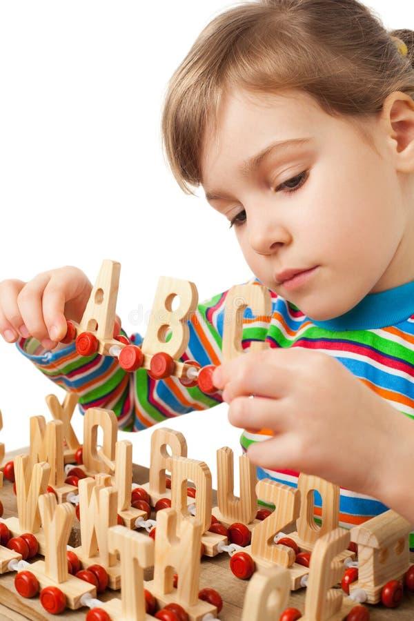 Het meisje wordt gespeeld door stuk speelgoed houten stoomlocomotief stock foto