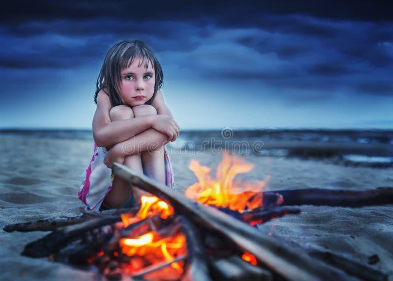 Het meisje wordt verwarmd door de brand stock foto's