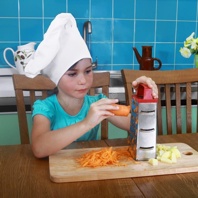 Het meisje wrijft wortel op rasp stock foto's