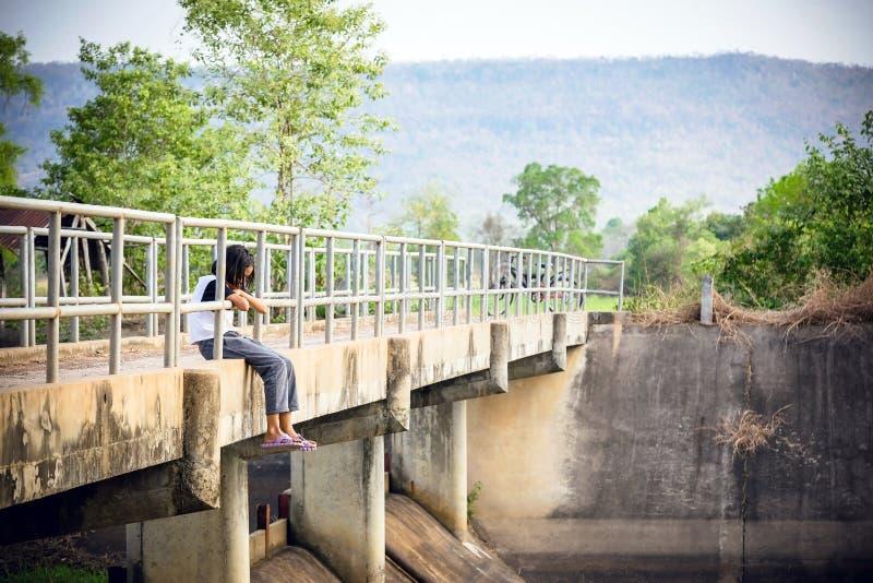 Het meisje zat op de brug in het bos stock foto
