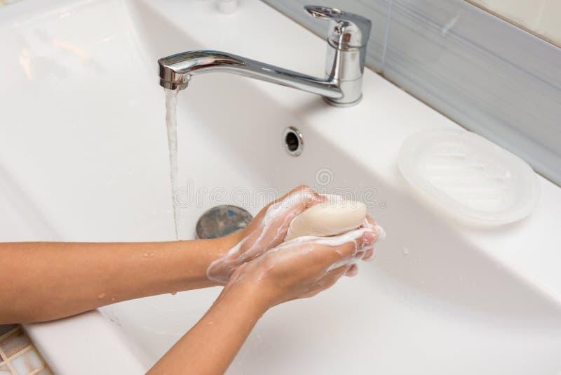 Het meisje zeept zorgvuldig haar handen met zeep, close-up in stock fotografie