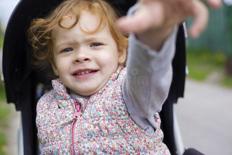 Het meisje is zenuwachtig in de wandelwagen stock fotografie