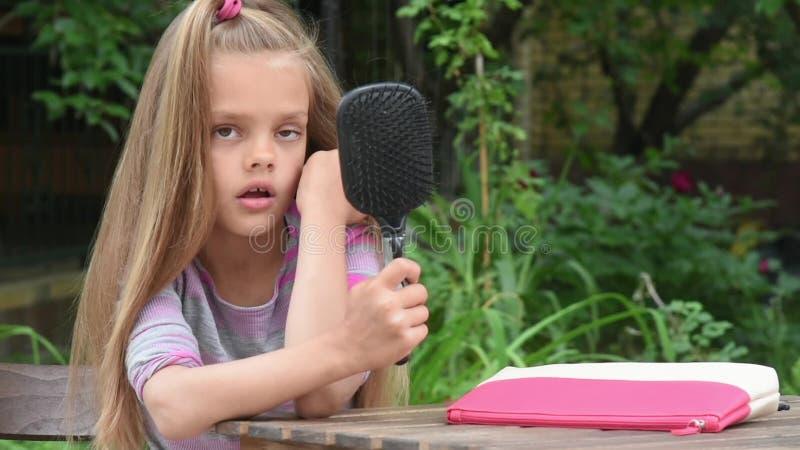 Het meisje ziet zich in een spiegel die in kam en het hamming wordt gebouwd stock footage