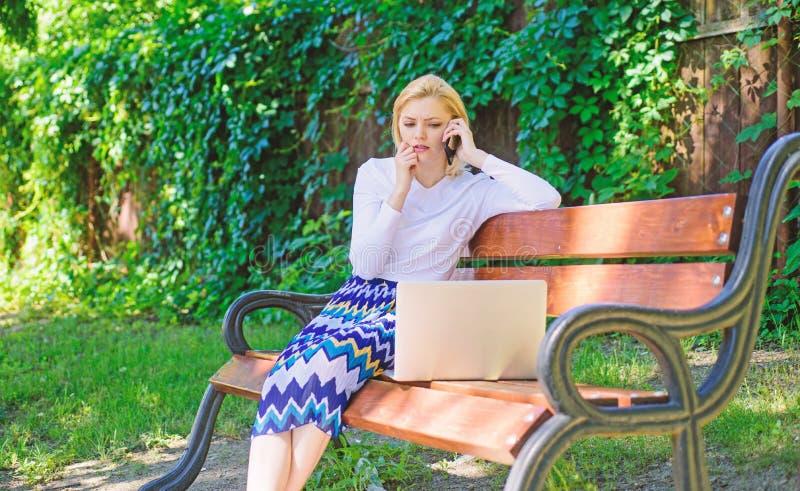 Het meisje zit bank met de telefoon van de notitieboekjevraag Sparen uw tijd met het virtuele winkelen Technologieën die het leve royalty-vrije stock fotografie