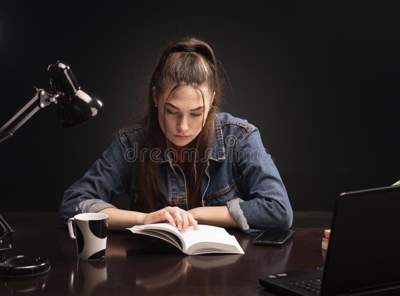 Het meisje zit bij de lijst en de studie royalty-vrije stock foto