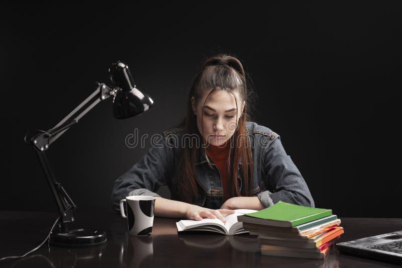 Het meisje zit bij de lijst en de studie royalty-vrije stock afbeeldingen