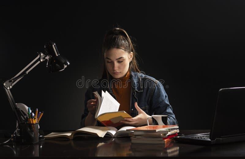 Het meisje zit bij de lijst en de studie stock foto's