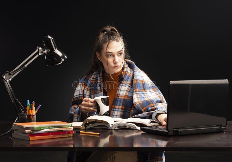 Het meisje zit bij de lijst en de studie stock afbeelding