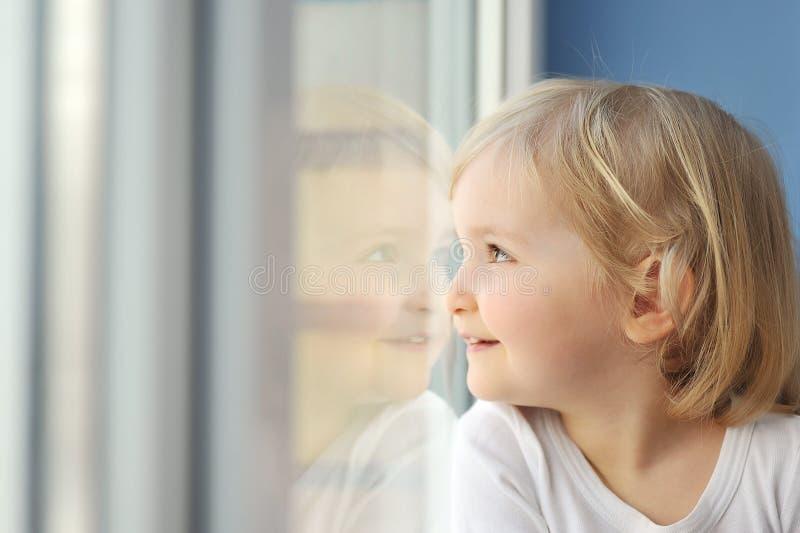 Het meisje zit bij venster royalty-vrije stock afbeelding