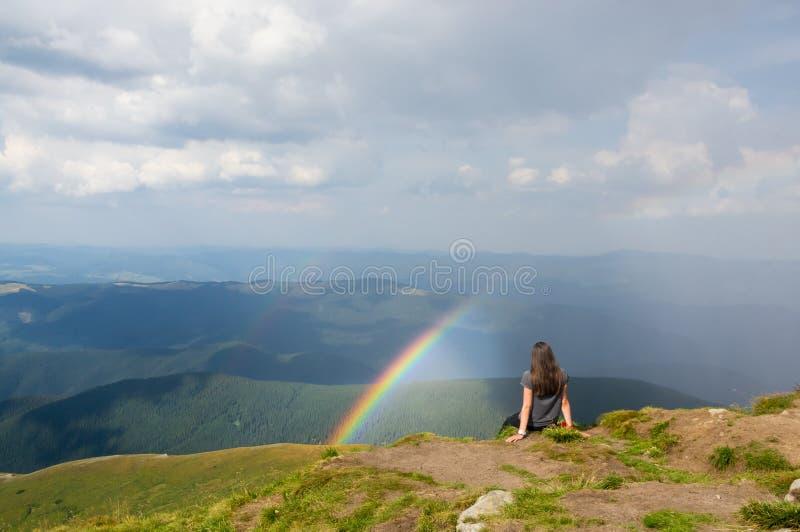 Het meisje zit in de bergen royalty-vrije stock afbeeldingen