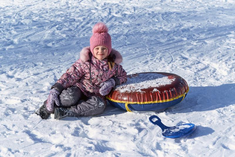 Het meisje zit in de sneeuw op een heldere Zonnige dag met de winterspeelgoed royalty-vrije stock fotografie