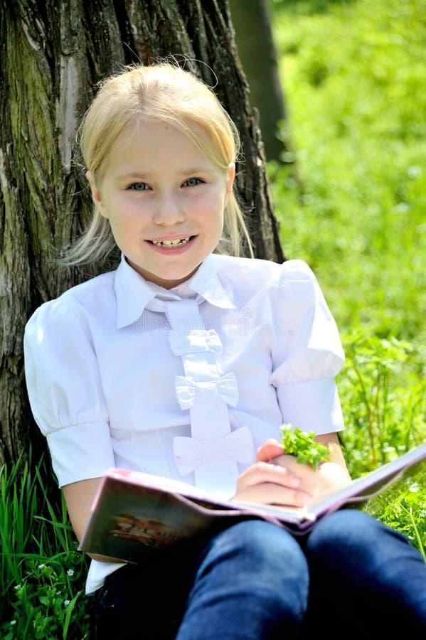 Download Het Meisje Zit Dichtbij Boom Met Boek In Handen Stock Foto - Afbeelding bestaande uit charming, kinderjaren: 54085222