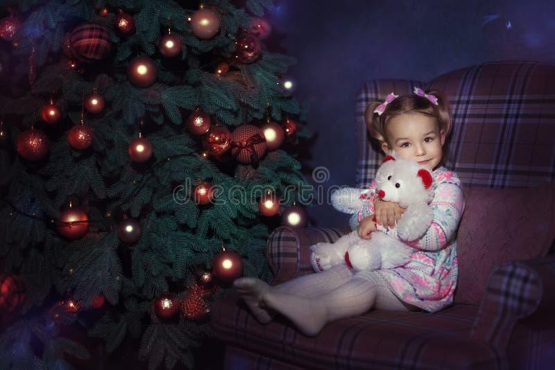 Het meisje zit dichtbij een Kerstboom royalty-vrije stock fotografie