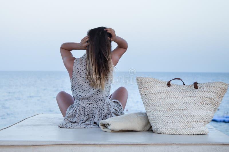 Het meisje zit door het overzees en ontspant stock foto