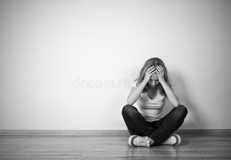 Het meisje zit in een depressie op de vloer dichtbij de muur stock fotografie