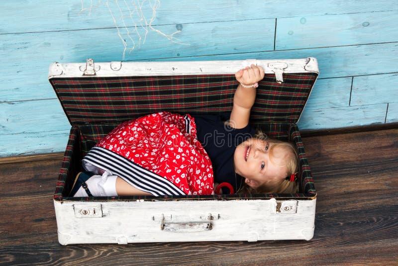 Het meisje zit in een koffer stock fotografie